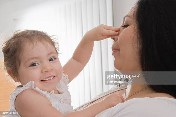 Hispanic baby girl touching mother's nose