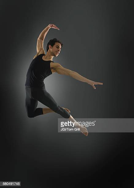 Hispanic ballet dancer leaping in mid-air