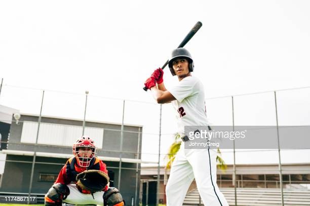 Hispanic baseball batter and catcher waiting for pitch