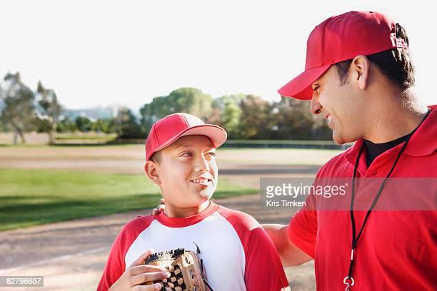 Hispanic baseball player and coach talking
