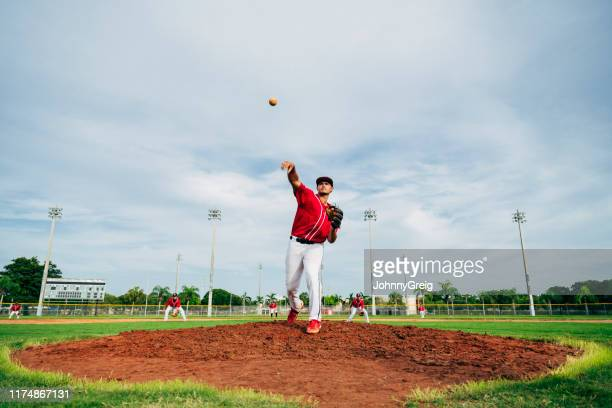 hispanic baseball player delivering a pitch from the mound - baseball team stock pictures, royalty-free photos & images