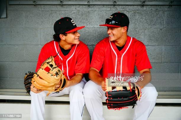 ダグアウトで並んで笑うヒスパニック系野球選手 - 高校野球 ストックフォトと画像