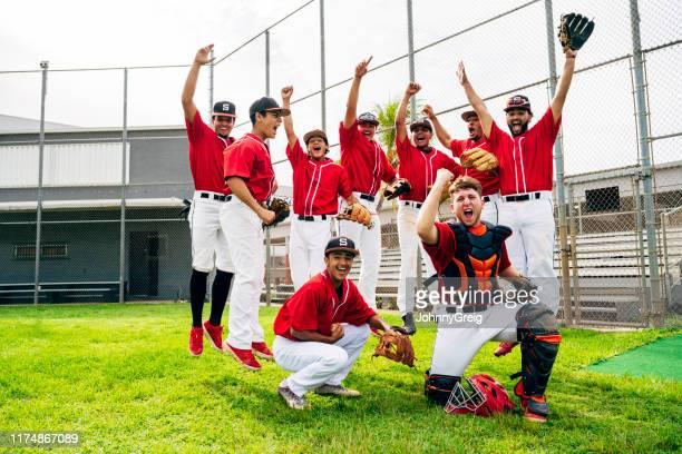 ヒスパニック系野球チームメイトがジャンプして勝利に身振り手振りをする - 野球チーム ストックフォトと画像