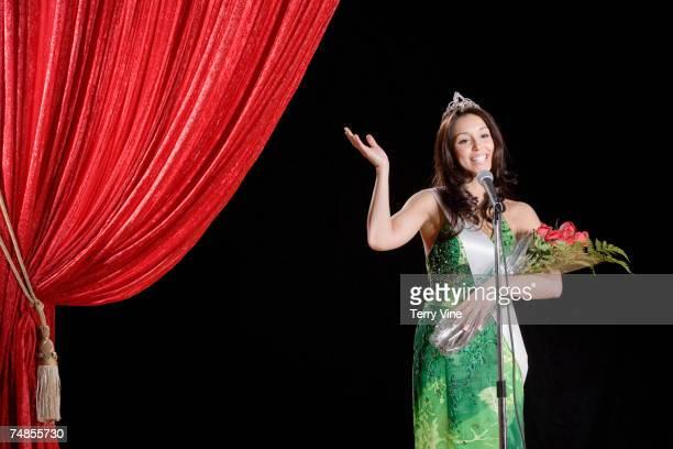 Hispanic beauty pageant winner waving on stage