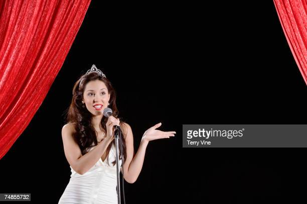 Hispanic beauty queen singing on stage