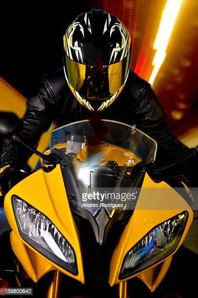 Hispanic biker in reflective helmet riding motorcycle