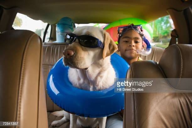 Hispanic boy and dog with beach gear in backseat of car