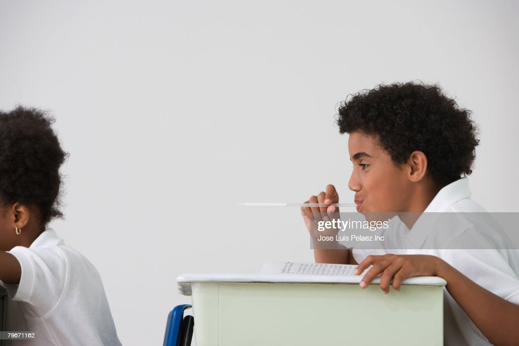 Hispanic boy blowing spitball on girl in class : Stock Photo