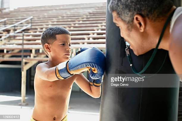 Hispanic boy boxing punching bag