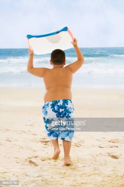 hispanic boy carrying boogie board to ocean - knaben in badehosen stock-fotos und bilder