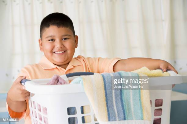 hispanic boy carrying laundry basket - chubby boy - fotografias e filmes do acervo