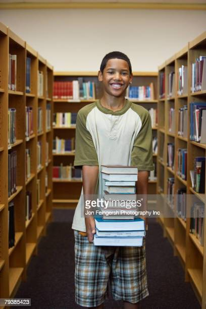 Hispanic boy carrying stack of library books