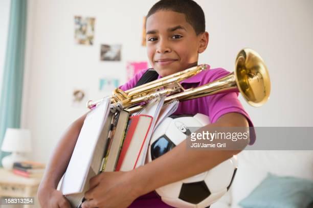 Hispanic boy carrying trumpet, books and soccer ball