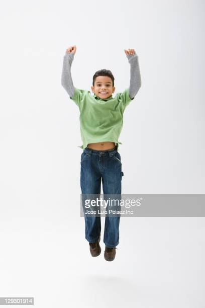 Hispanic boy cheering and jumping