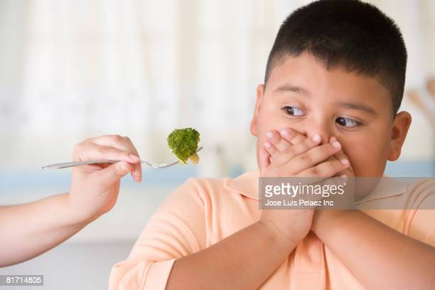 hispanic boy covering mouth next to broccoli - grasa nutriente fotografías e imágenes de stock