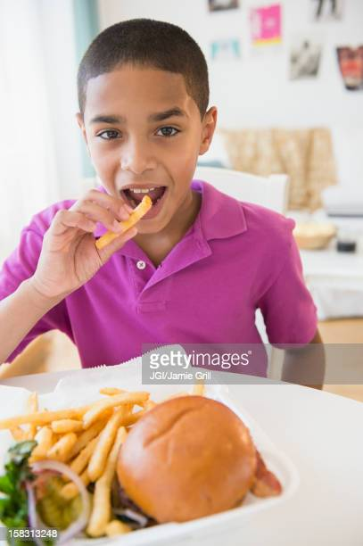Hispanic boy eating hamburger and french fries