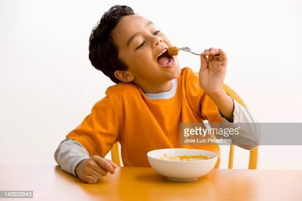 Hispanic boy eating pasta