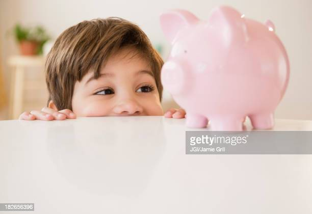 Hispanic boy examining piggy bank