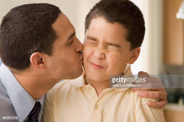 Hispanic boy grimaces as father kisses him