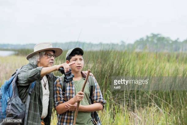 Hispanic boy hiking with grandfather, bird watching