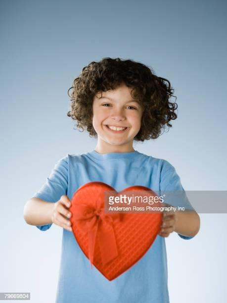Hispanic boy holding heart-shaped gift