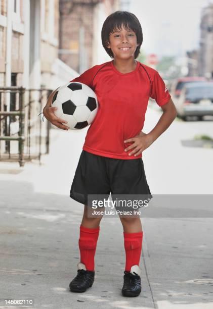 Hispanic boy holding soccer ball on city sidewalk