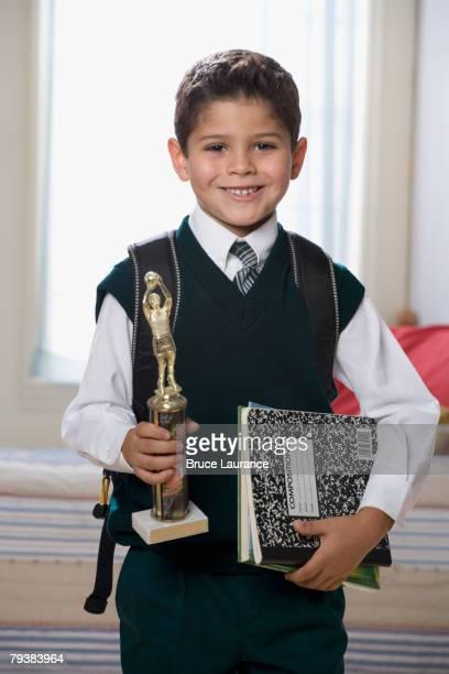 Hispanic boy holding trophy and school books
