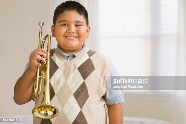 Hispanic boy holding trumpet