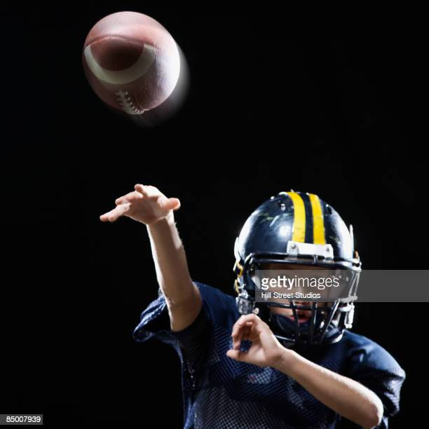 hispanic boy in football uniform throwing ball - quarterback stock photos and pictures