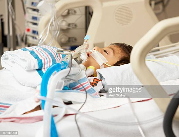 hispanic boy in intensive care unit bed - equipamento respiratório - fotografias e filmes do acervo