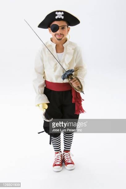 Hispanic boy in pirate costume holding sword