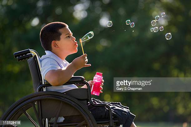 Hispanic boy in wheelchair blowing bubbles