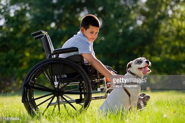 Hispanic boy, 8, in wheelchair with dog