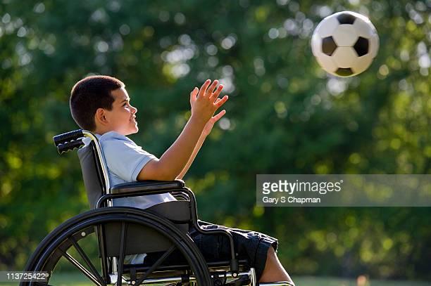 Hispanic boy, 8, in wheelchair with soccer ball
