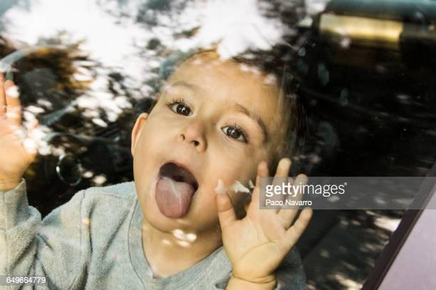 Hispanic boy licking car window