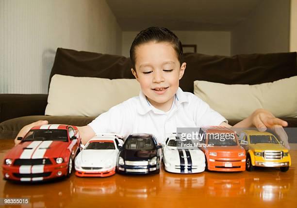Hispanic boy lining up toy cars