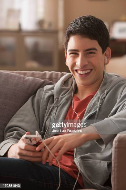 Hispanic boy listening to mp3 player on sofa