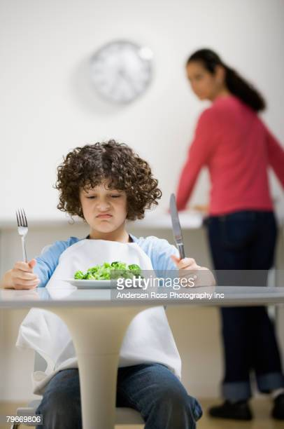 Hispanic boy making face at salad