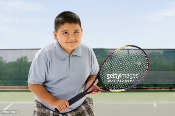 Hispanic boy playing tennis