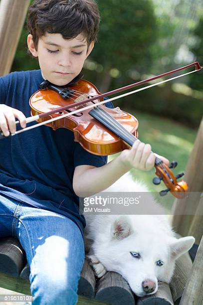 Hispanic boy playing violin with dog
