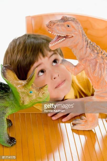 Hispanic boy playing with toy dinosaurs