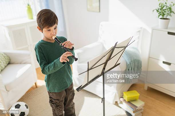 hispanic boy practicing recorder in living room - recorder musical instrument stock photos and pictures