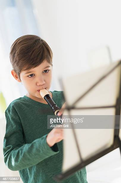Hispanic boy practicing recorder