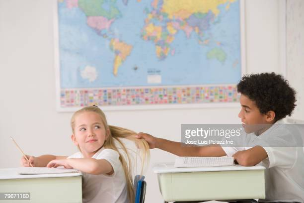Hispanic boy pulling on girl's hair in class