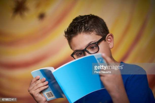 hispanic boy reading blue book - preadolescente fotografías e imágenes de stock