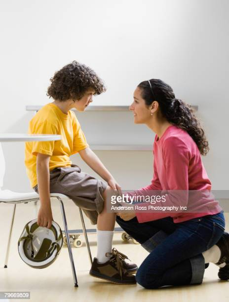 hispanic boy showing skinned knee to mother - knees together stock photos and pictures