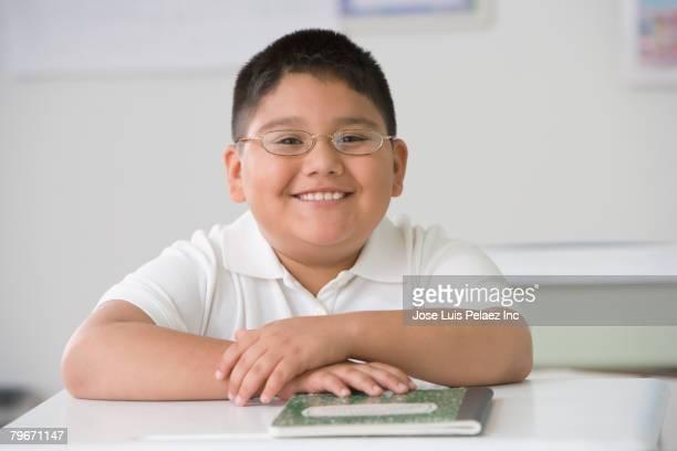 Hispanic boy sitting at school desk