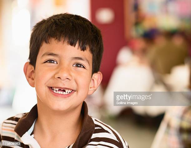 Hispanic boy smiling with gap in his teeth