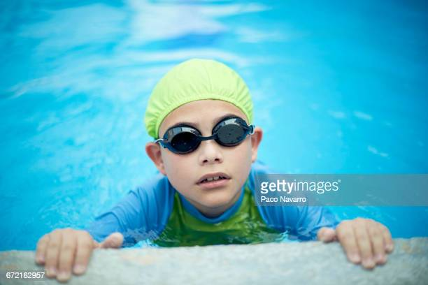 Hispanic boy swimming with swimming cap and goggles