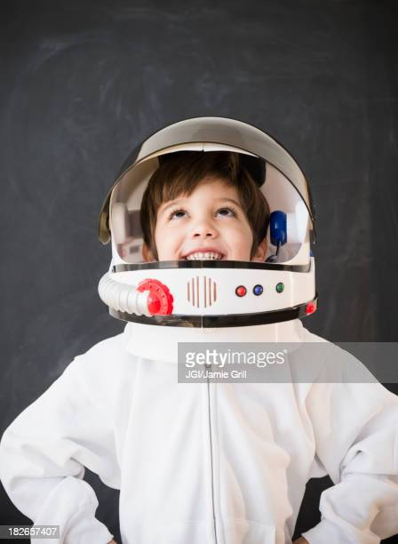Hispanic boy wearing space helmet in classroom